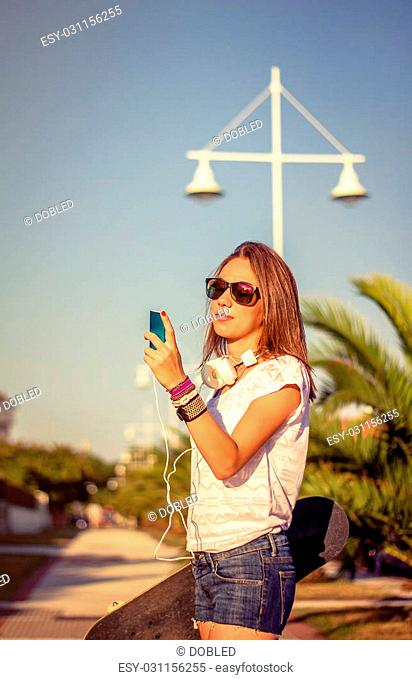 Portrait of beautiful young girl with skateboard and headphones looking her smartphone outdoors. Warm tones edition