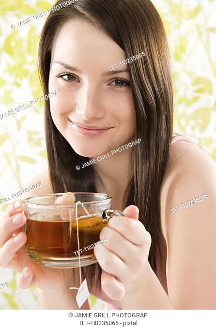 Portrait of smiling young woman holding tea cup