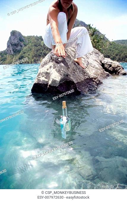 Young woman reaching for a message in a bottle