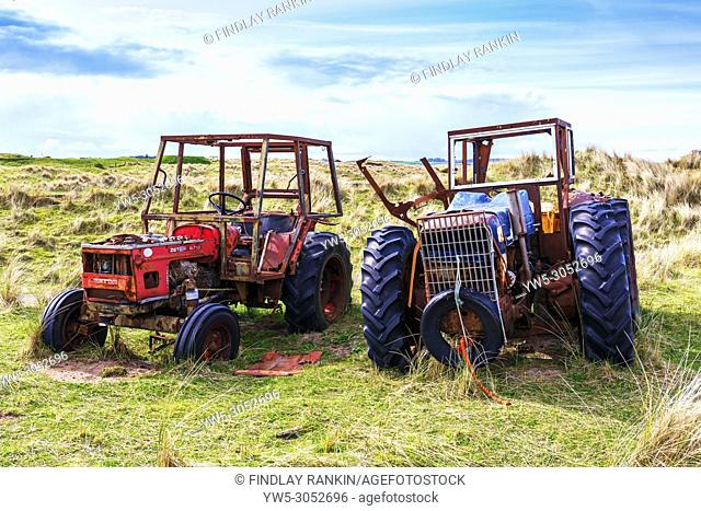Two old and abandoned farm tractors in a field near Goswick, Northumberland, England, UK