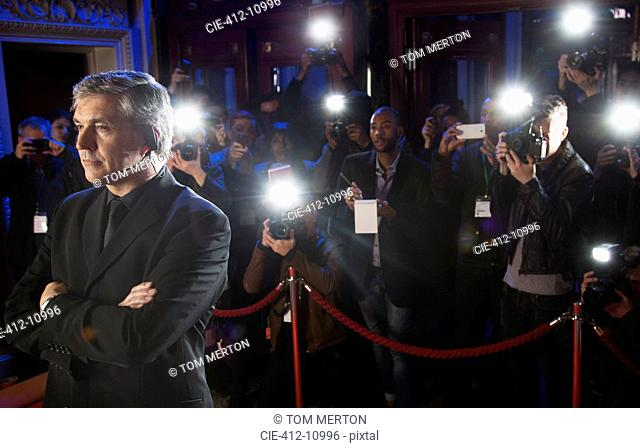 Paparazzi using flash photography behind bodyguard at red carpet event