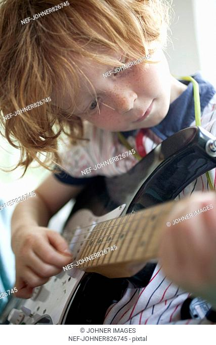Redheaded boy playing electric guitar, Sweden