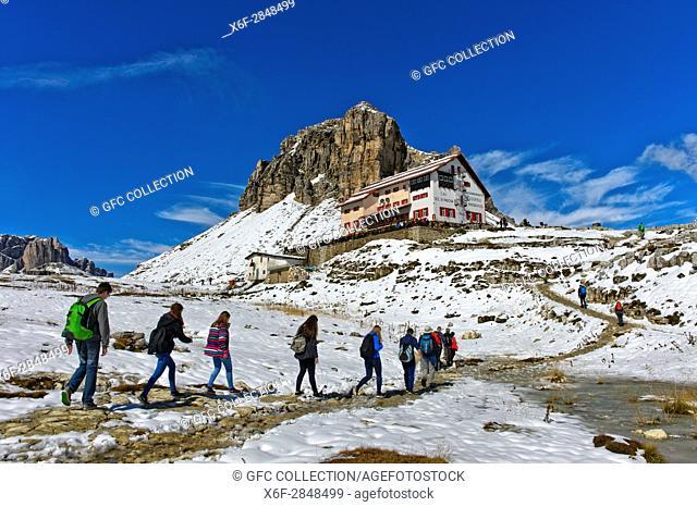 Hikers on the way to the Dreizinnenhütte, Rifugio Locatelli hut, snow-covered peaks Sextener Stein, Sasso di Sesto,and Tower of Toblin, Torre di Toblin