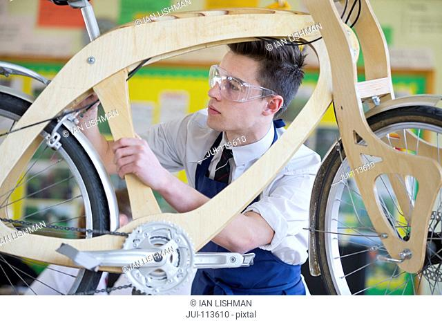 High school student assembling bicycle in shop class