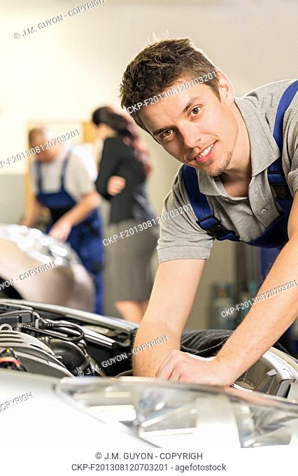 Portrait of young mechanic repairing car