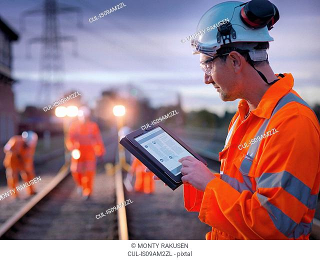 Railway maintenance worker using digital tablet at night