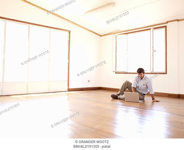 Hispanic businessman using laptop on floor in empty office