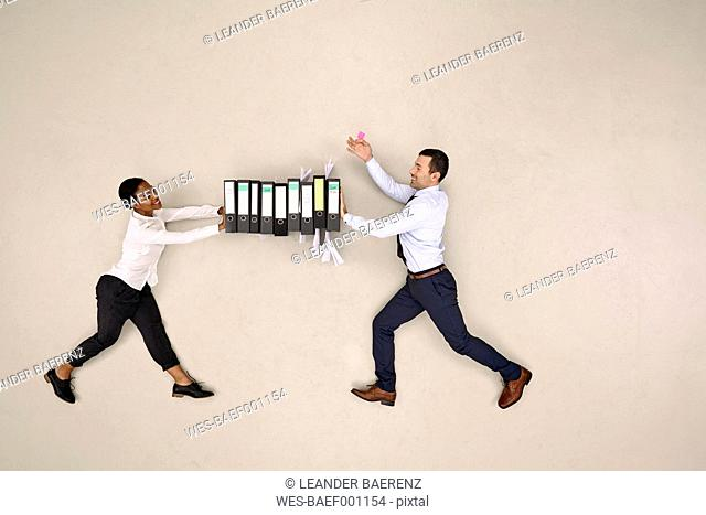 Two colleagues pushing folders together
