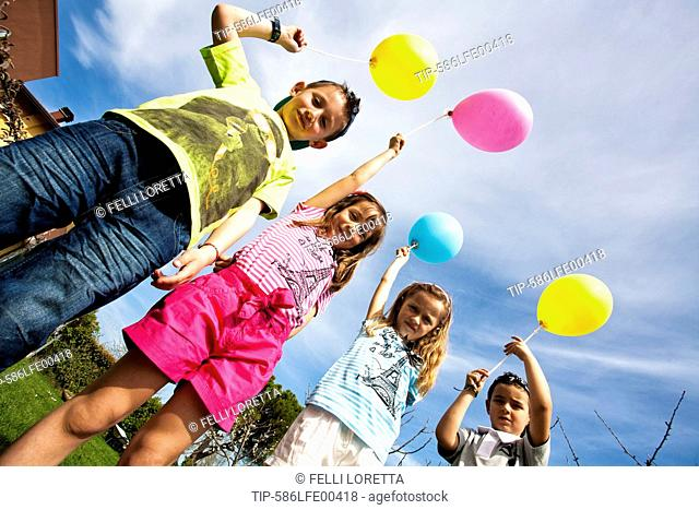 children with multi coloured balloon