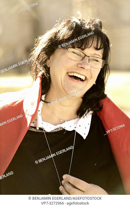 happy mature woman laughing outdoors in sunlight, in Cottbus, Brandenburg, Germany