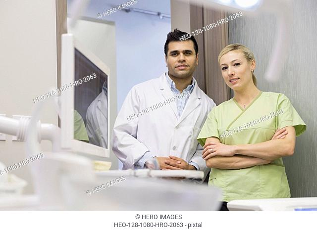 Portrait of confident dentist and assistant in office
