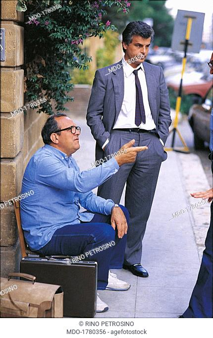 Damiano Damiani and Michele Placido on the set of Pizza connection. Italian director Damiano Damiani giving some directions to Italian actor Michele Placido on...
