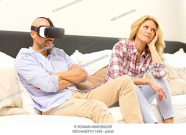 Man wearing Virtual Reality Glasses sitting on couch beside his bored wife
