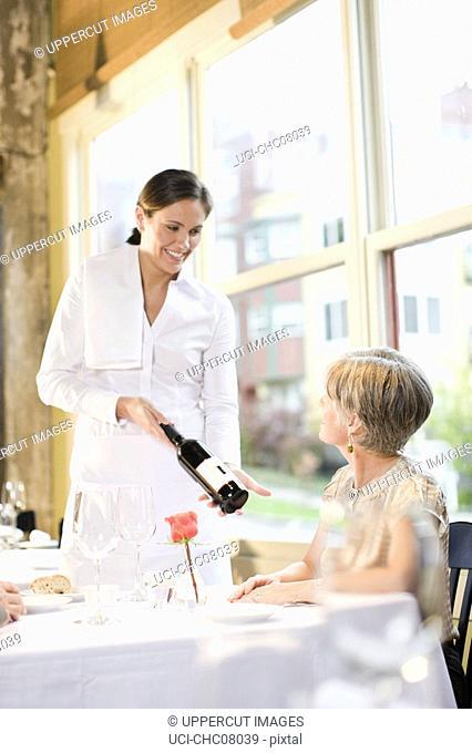 Waitress showing wine to couple