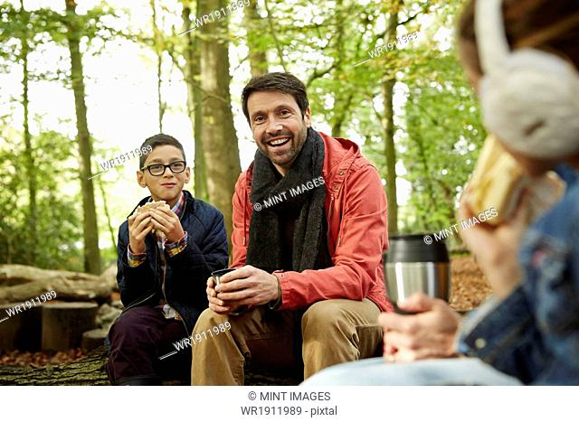 Beech woods in Autumn. Three people, a father and two children having a picnic