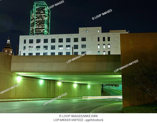 Underpass with brightly lit buildings above