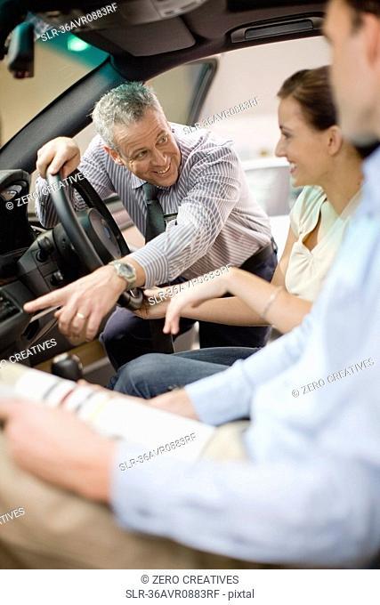 Salesman showing off car in showroom