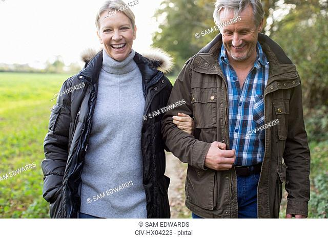 Happy mature couple walking arm in arm in park
