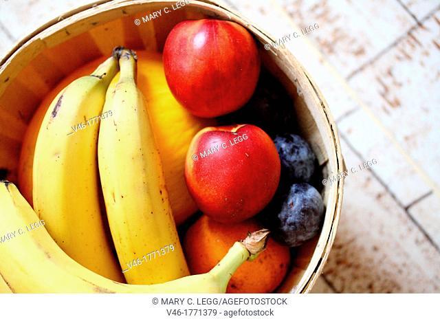 Bananas and nectarines in basket  Bananas, nectarines, plums and melon in small bushel basket