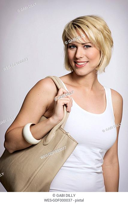 Portrait of young woman holding handbag, smiling, close up