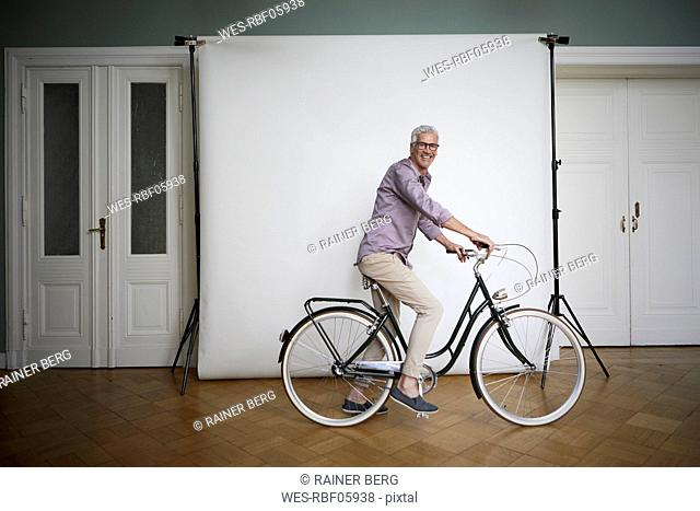 Portait of mature man posing on bicycle at projection screen