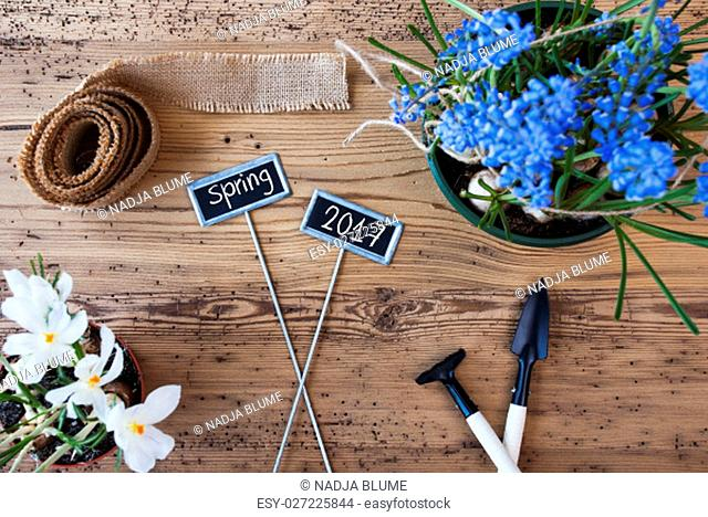 Two Signs With English Text Spring 2017. Spring Flowers Like Grape Hyacinth And Crocus. Gardening Tools Like Rake And Shovel. Hemp Fabric Ribbon