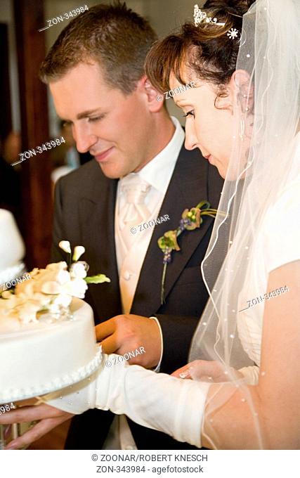 Junges Brautpaar schneidet die Hochzeitstorte an