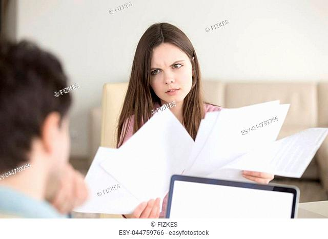 Couple discussing domestic bills, bank statements, woman holding papers looking angry and frustrated, found error in incorrect documents, contracts