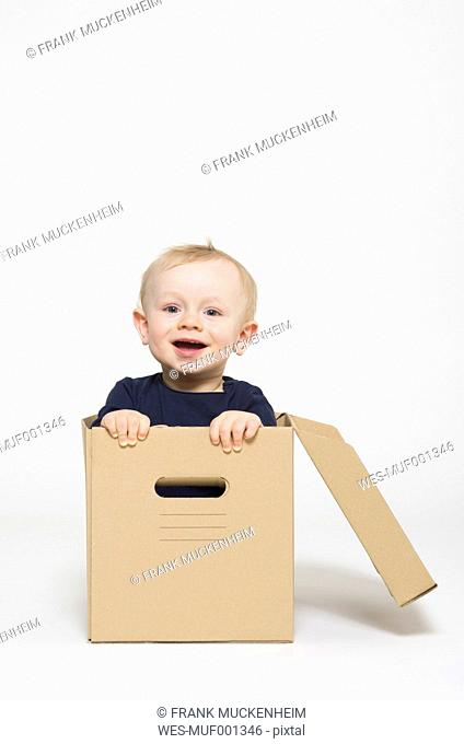 Portrait of baby boy sitting in box, smiling
