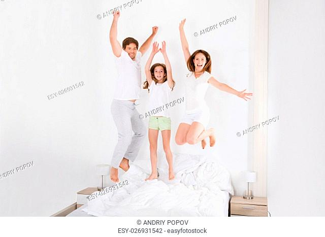 Happy Family Jumping On Bed Together In Their Bedroom