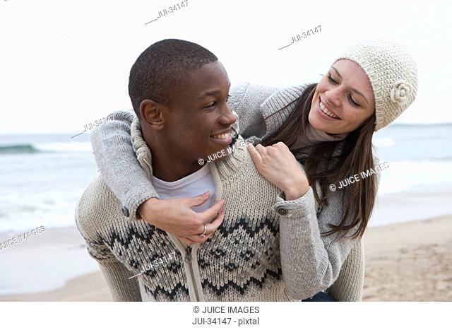 Smiling young couple piggybacking on beach
