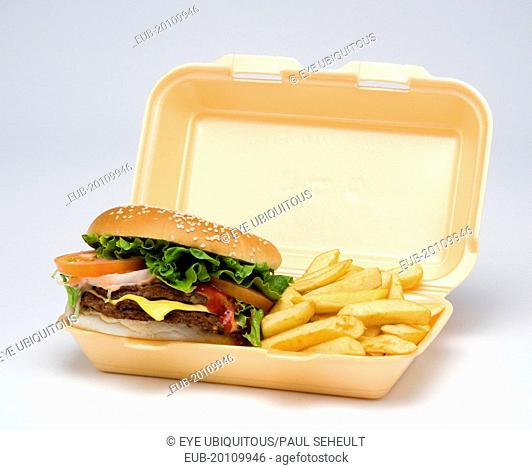 Food, , , Double cheesburger with salad and tomato ketchup in a bun with potato chips inside a polystyrene foam box on a white background