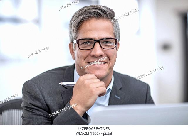 Businessman with spectacles sitting in office, smiling