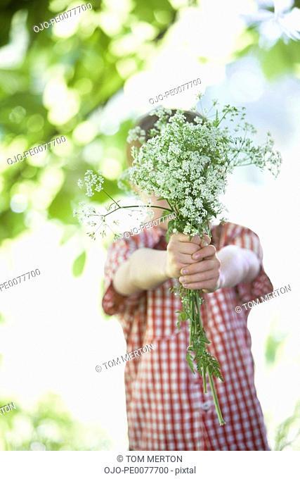 Boy offering bouquet of flowers