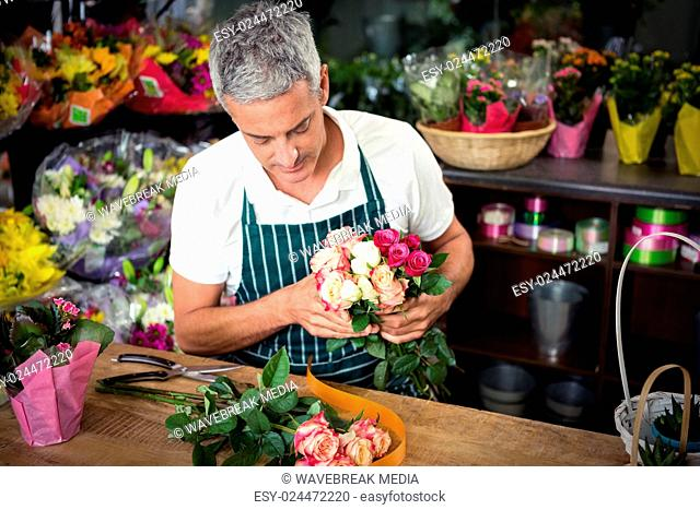 Male florist holding bunch of roses