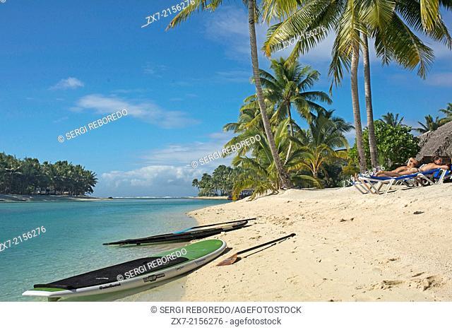 Aitutaki. Cook Island. Polynesia. South Pacific Ocean. Some tourists take a sun bath on the beach of Aitutaki Lagoon Resort & Spa Hotel