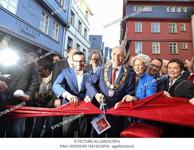 28 September 2018, Hessen, Frankfurt-Main: Peter Feldmann (SPD, M), Lord Mayor of the City of Frankfurt am Main, symbolically cuts a red ribbon in the presence...