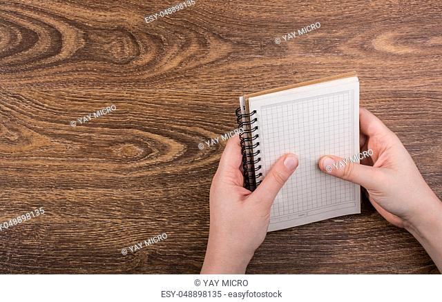 White notebook in hand on a brown color background