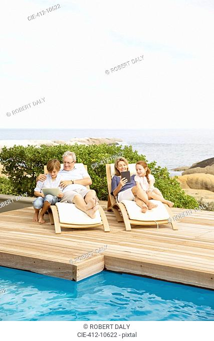 Older couple and grandchildren relaxing by pool