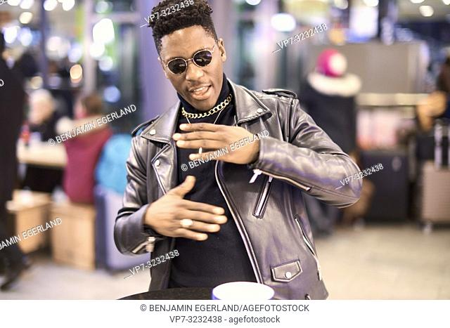 young fancy man gesticulating body language, with coffee cup at bar table, African descent, in Munich, Germany
