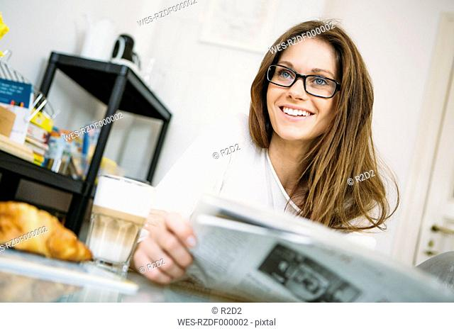 Portrait of smiling woman with newspaper