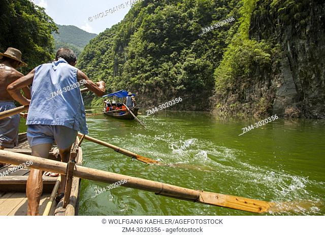 Chinese men rowing a traditional Sampan boat near Badong on the Shennong stream, a tributary of the Yangtze River at the Wu Gorge (Three Gorges) in China