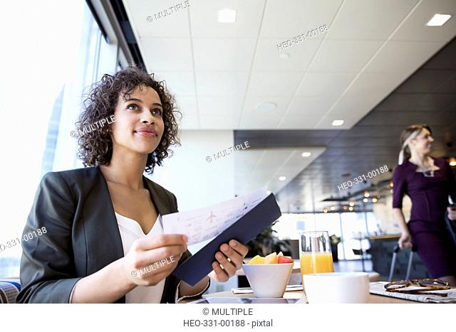 Businesswoman with digital tablet and airplane ticket at breakfast table in airport lounge