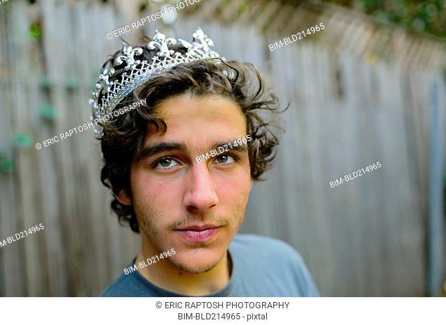 Hispanic man wearing crown in backyard