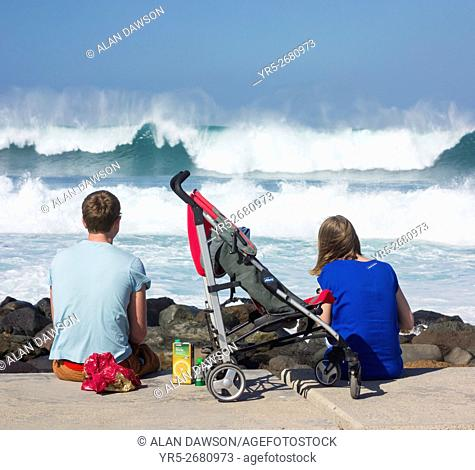 Young family wave watching on Las Canteras beach in Las Palmas, Gran Canaria, Canary Islands, Spain