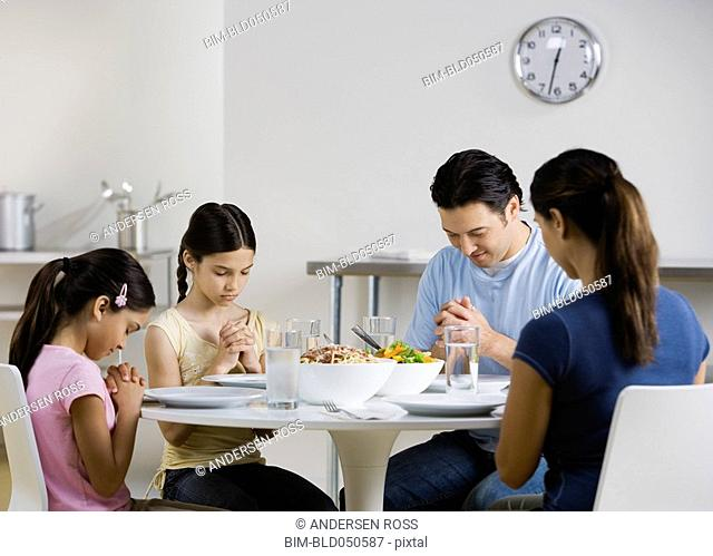 Multi-ethnic family praying at dinner table