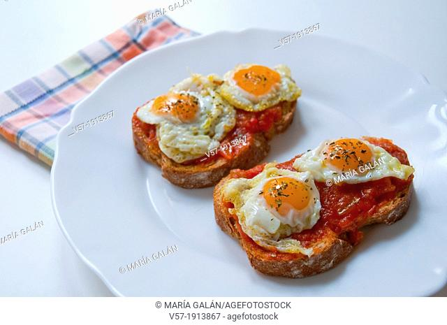 Spanish tapa: fried quail eggs with pisto manchego on toast