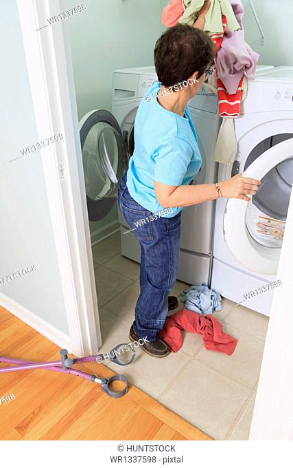 Woman with cerebral palsy washing clothes in the laundry room