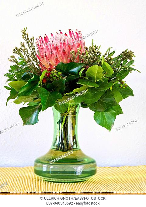 Still life of a wonderful bouquet of a single Protea blossom and greenery in a green vase