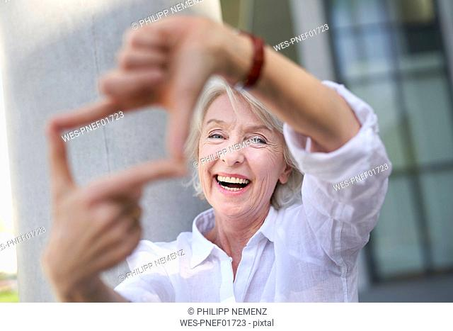 Portrait of laughing mature woman shaping frame with her fingers